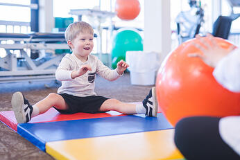 physical therapist works with a young boy with autism in an open floor clinic