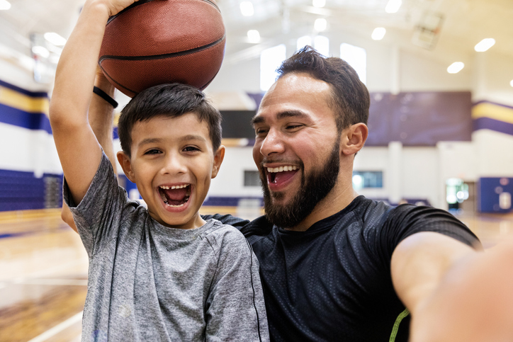 school basketball coach laughs with child with autism