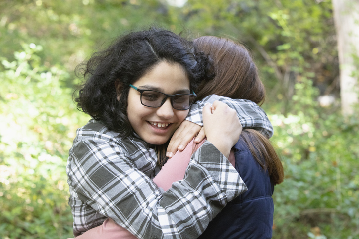 sisters with autism hugging