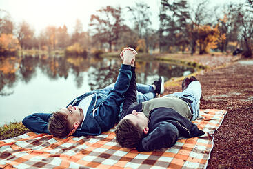 two boys holding hands on a picnic autism