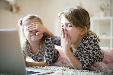 two girls with autism with laptop using senses of touch smell and sight