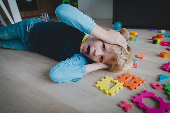 young autistic boy shouting with toys scattered around