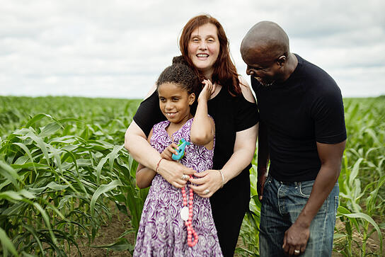 young autistic girl is posing for a family portrait with her mother and father in a corn field