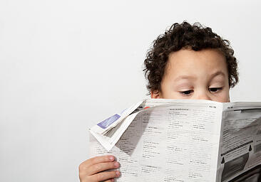young boy autism reading newspaper