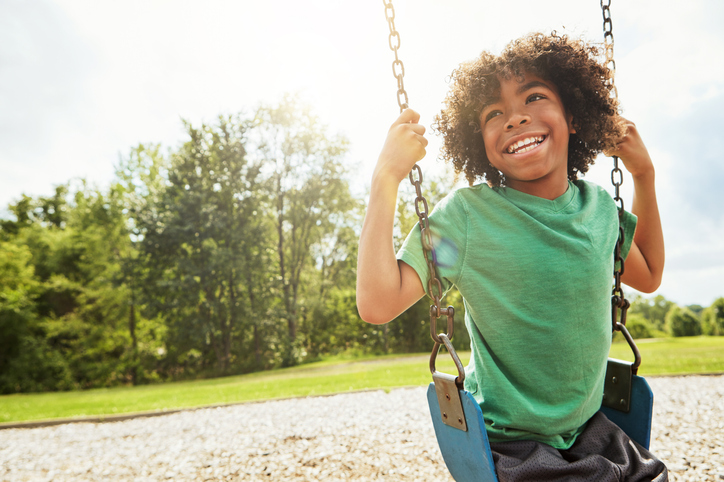 young boy with autism playing on a swing at the park