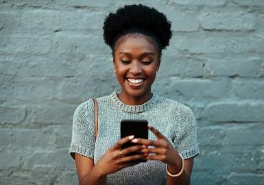 young creative businesswoman using her cellphone during coronavirus lockdown