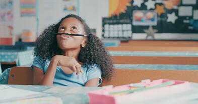 young girl with autism looking bored while playing at a school desk